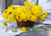 Bouquet of dandelions in a basket — Stock Photo