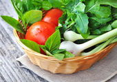Fresh vegetables and greenery are in a basket on a old wooden background — Stock Photo