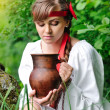 Beautiful young girl with a ceramic jug at the well — Stock Photo #47366283
