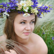 Beautiful young woman with flower wreath in the grass of feather-grass outdoors — Stock Photo #47366345