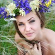 Beautiful young woman with flower wreath in the grass of feather-grass outdoors — Stock Photo #47366353