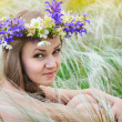Beautiful young woman with flower wreath in the grass of feather-grass outdoors — Stock Photo #47366357