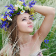 Beautiful young woman with flower wreath in the grass of feather-grass outdoors — Stock Photo #47366359