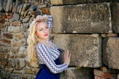 Sexy blond woman leaning against ancient stone wall — Stock Photo