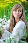 Beautiful young woman on the meadow with white flowers on a warm summer day — Stock Photo