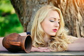 Portrait of a beautiful blonde woman with a ceramic jug — Stock Photo