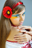 Portrait of a woman with creative makeup Ukrainian flag on her face in the Ukrainian national costume — Stock Photo