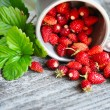 Fresh wild strawberries on an old wooden table — Stock Photo #48138939