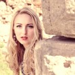 Beautiful blond woman leaning against ancient stone wall — Stock Photo #48847183