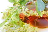Teapot with linden tea and flowers, close-up — Stock Photo
