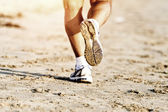 Runner feet running on beach closeup on shoe — Stock Photo