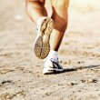 Stock Photo: Runner feet running on beach closeup on shoe