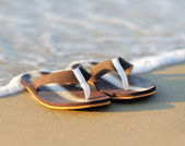 Flip flops on a sandy ocean beach — Stock Photo