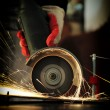 Worker cutting metal with grinder - Stock Photo