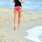 Running legs and shoes of runner jogging on beach — Stock Photo