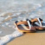 Flip flops on a sandy ocean beach — Stock Photo #23976459