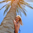 Girl stands near by palm tree — Stock Photo