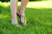 Woman legs walking on grass — Stock Photo