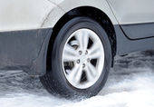 Dirty car wheel stands on winter road — 图库照片