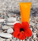 Stack of pebbles, cream and flower — Stock Photo