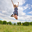 Young girl jumping high in a summer field — Stock Photo