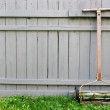 Stock Photo: Vintage push reel lawn mower with fence background