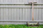 フェンスの背景を持つヴィンテージ プッシュ リール芝刈り機 — ストック写真