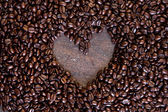 Whole coffee beans as background with heart on a wooden table — Zdjęcie stockowe