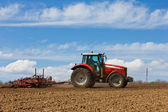 Farmer plowing the field. Cultivating tractor in the field. Red farm tractor with a plow in a farm field. Tractor and Plow — Stock Photo