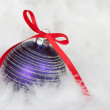 Purple christmas bauble on feathers — Stock Photo #14118508