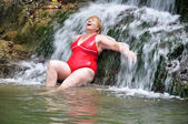Adult woman in red swimsuit enjoying a waterfall — Stock Photo