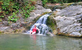 Adult woman in red swimsuit near a waterfall — Stock Photo