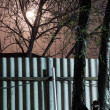 Stock Photo: Night photography. Moon over the fence and trees