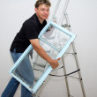 A man with a window on a ladder on a white background — Stock Photo #15837375