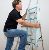 A man with a window on a ladder on a white background — Stockfoto