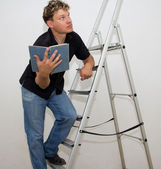A man with a ladder and a book — Stock Photo