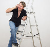 A man with a cell on a stepladder on a white background — Stock Photo