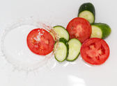 Cucumber and tomato in water on white background — Stock Photo