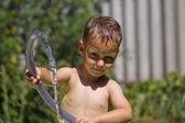 мальчик брызгает водой из шланга — Стоковое фото