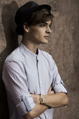 Handsome man casually leaning against the wall — Stock Photo