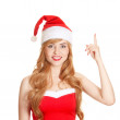 Beautiful woman wearing a Santa's hat point out on copyspace - Stock Photo