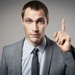 Young businessman criticizing on gray background — Stock Photo #14415105