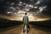Business man standing in the middle of the road. Dramatic sky ab — Stock Photo