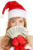 Christmas woman holding dollars banknotes wearing Santa hat — Stock Photo