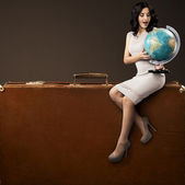Lovely Woman With Globe In Hands Sitting On Huge Retro Suitcase. — Stock Photo