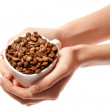 Woman hands holding coffee beans in cup isolated - Stock Photo