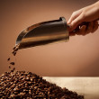 Hand holding steel scoop and coffee beans - Stock Photo
