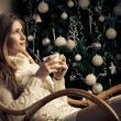 Beautiful woman with cup of coffee in chair. Christmas  decorati — 图库照片