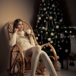 Beautiful woman with cup of coffee in chair. Christmas decorati — Stock Photo