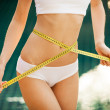 Woman measuring her waistline. Perfect Slim Body. Outdoor - Stock Photo